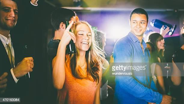 Mulher jovem feliz em uma festa segurando seu Cerveja