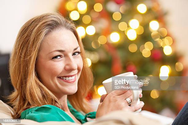 Happy Young Woman at Christmas Enjoying Time in Living Room