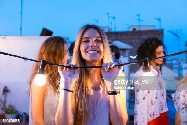 Happy young woman at the rooftop party
