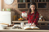 Happy young woman baking pie in loft kitchen at home, using book with recipe. Mockup, copy space