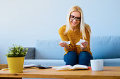 Happy young woman checking bills at home sitting on sofa