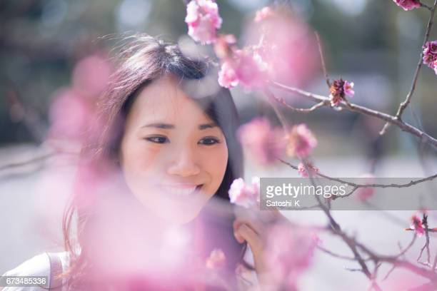 Happy young woman closely looking at plum blossoms