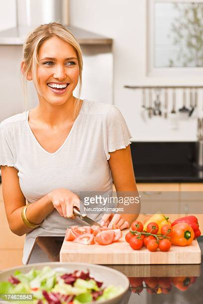 Happy young woman cutting vegetables