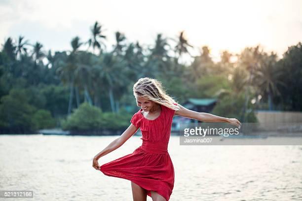 Heureuse jeune femme dansant sur la plage au coucher de soleil