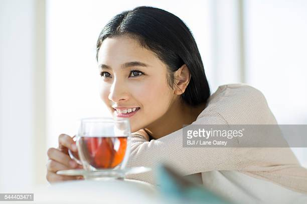 Happy young woman drinking black tea