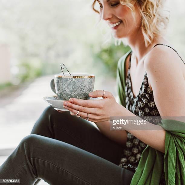 Felice giovane donna bere tè