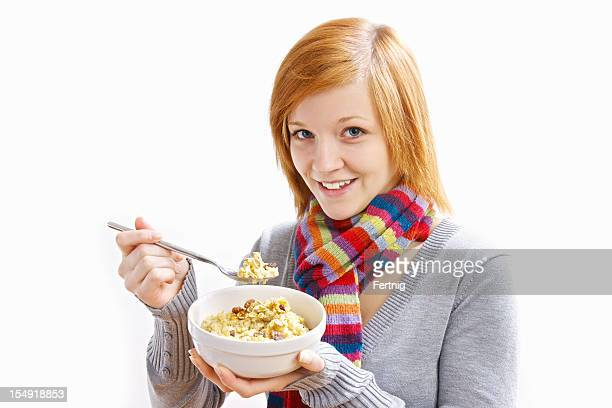 Happy young woman eating a bowl of oatmeal
