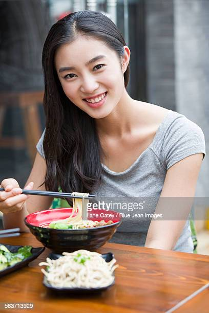 Happy young woman eating noodles