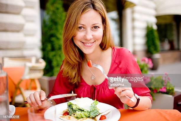 Glückliche junge Frau Essen im Freien