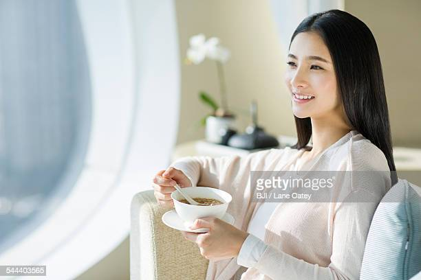 Happy young woman eating porridge on sofa