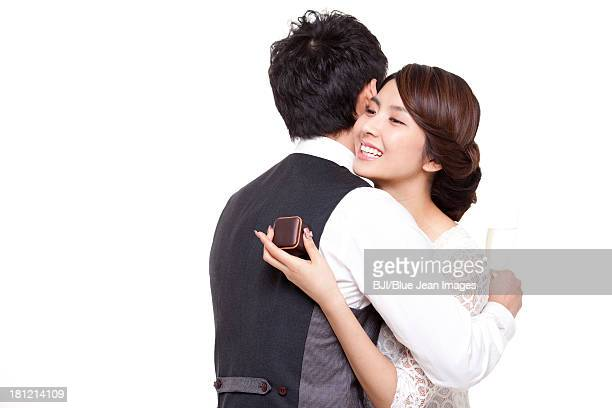 Happy young woman embracing young man with a ring in hand