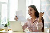 Happy young woman student or employee excited by reading good news in paper letter about new job, great deal, positive exam result, celebrating success or opportunity offered in written notification