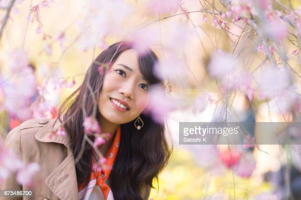 Happy young woman getting closer to cherry blossoms