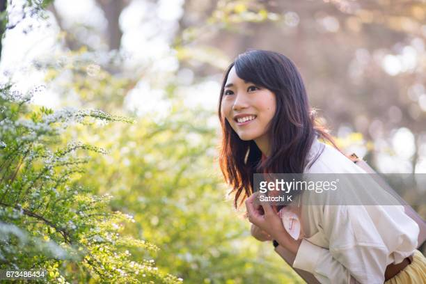 Happy young woman getting closer to green leaves
