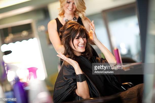 Felice giovane donna guida capelli come Updo nel salone