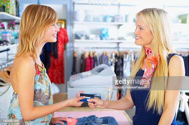 Feliz joven mujer dando tarjeta de crédito para shopkeeper