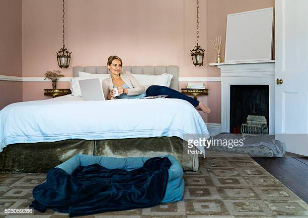 Happy young woman having coffee in bed