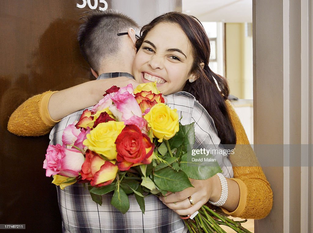 Happy young woman having received flowers. : Stock Photo
