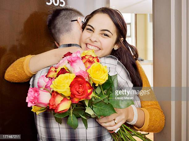 Happy young woman having received flowers.