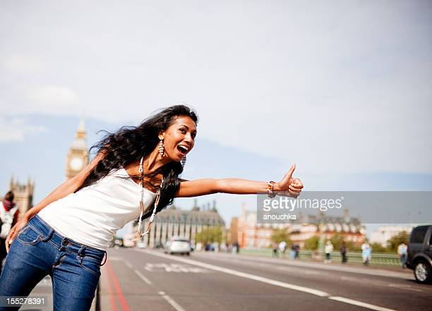 Happy Young Woman Hitchhiking on Westminster Bridge, London