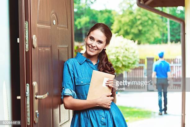 Glückliche junge Frau hält einen Umschlag