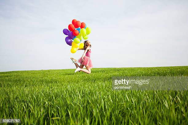 Happy young woman holding balloons and jumping on the field
