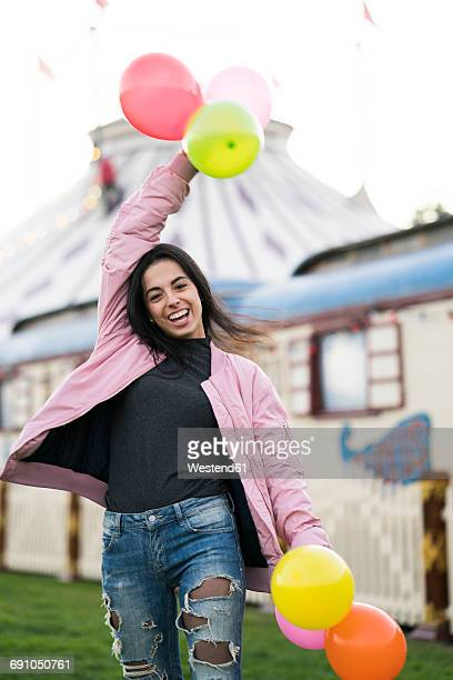 Happy young woman holding balloons outdoors