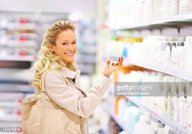 Happy young woman holding beauty product in mall