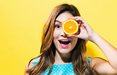 Happy young woman holding oranges on a yellow background