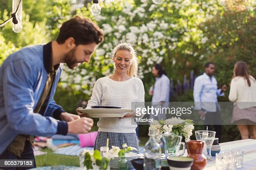 Happy young woman holding plates while enjoying summer party with friends in yard