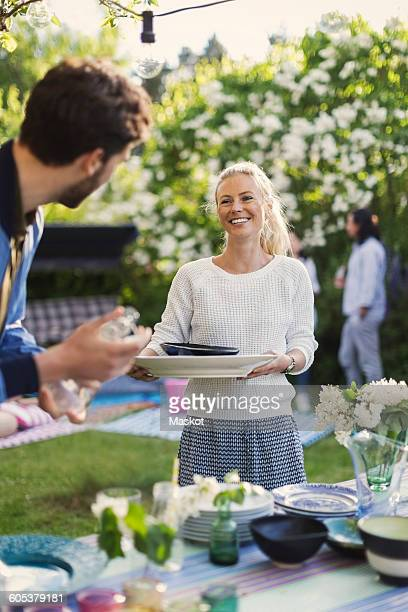 Happy young woman holding plates while looking at friend in yard during summer party