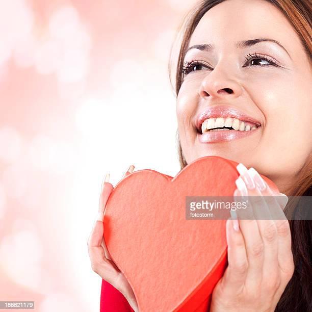 Glückliche junge Frau hält Rotes Herz Valentinstag