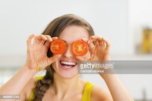 Glückliche junge Frau hält zwei rote vor Augen : Stock-Foto