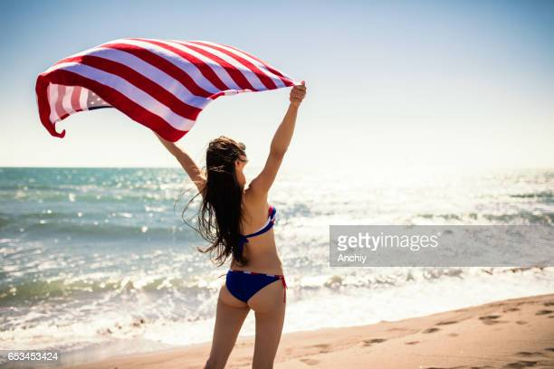 Happy young woman in bikini running on the beach with the USA flag in her hands