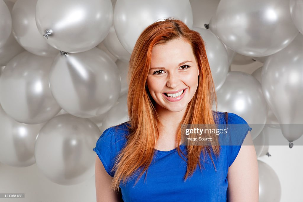Happy young woman in front of balloons : Stock Photo