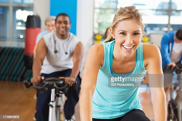 Happy young woman in her fitness cycling class