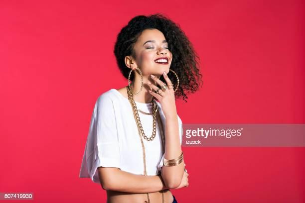 Heureuse jeune femme dans un style hip hop sur fond rouge
