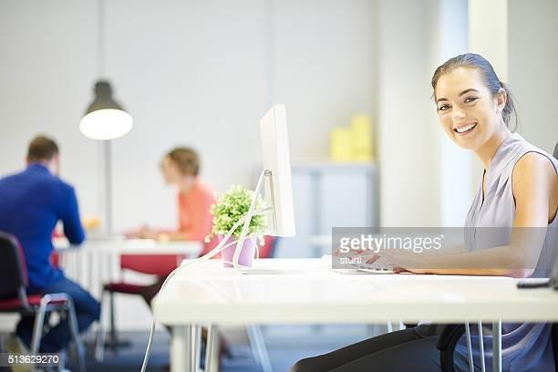 Glückliche junge Frau im Büro Arbeitsplatz