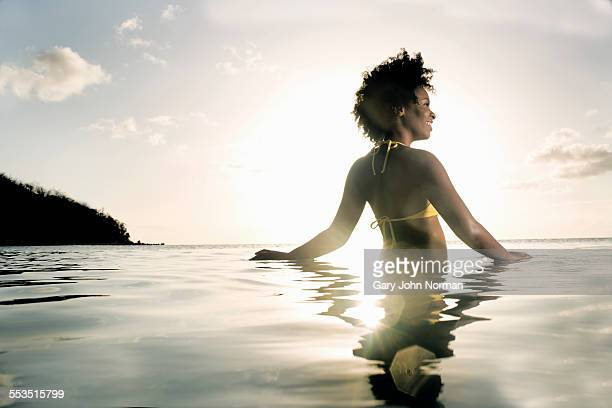 Happy young woman in the calm ocean, low light.