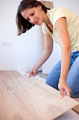 Happy young woman installing laminate flooring in new apartment or house. Home improvement and renovation concept