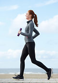 Happy young woman jogging with weights in hands