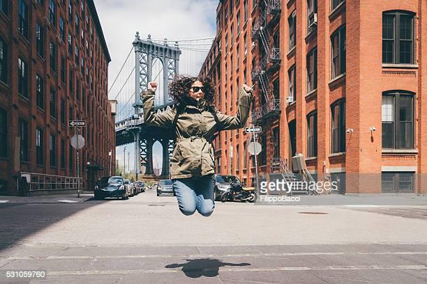 Heureuse jeune femme sautant à proximité du pont de Manhattan à New York