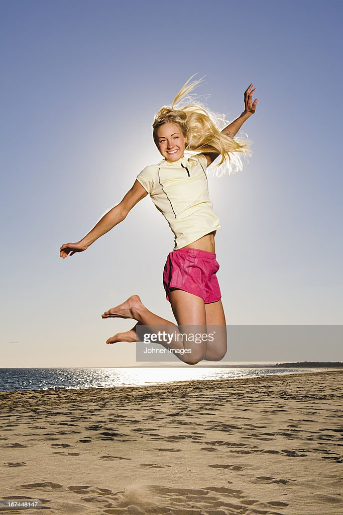 Happy young woman jumping on beach : Stock Photo