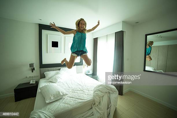 Happy young woman jumping on bed