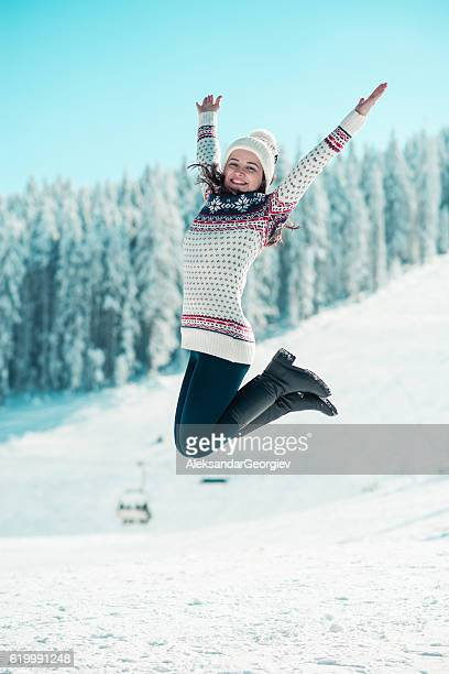 Happy Young Woman Jumping on the Snow with Raised Arms