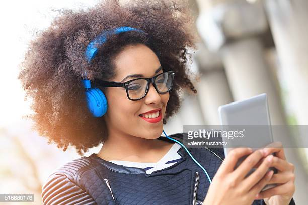 Happy young woman listening music on digital tablet