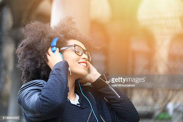 Happy young woman listening music on street-sunlight