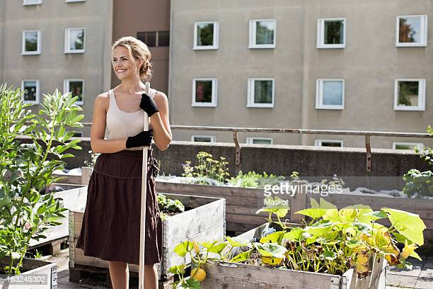 Happy young woman looking away while standing at urban garden