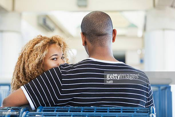 Happy young woman looking over her boyfriend's shoulder