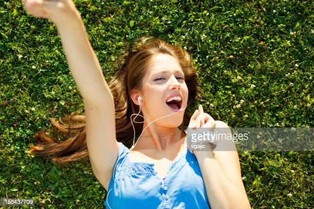 Felice giovane donna sdraiata sull'erba e ascoltare musica.